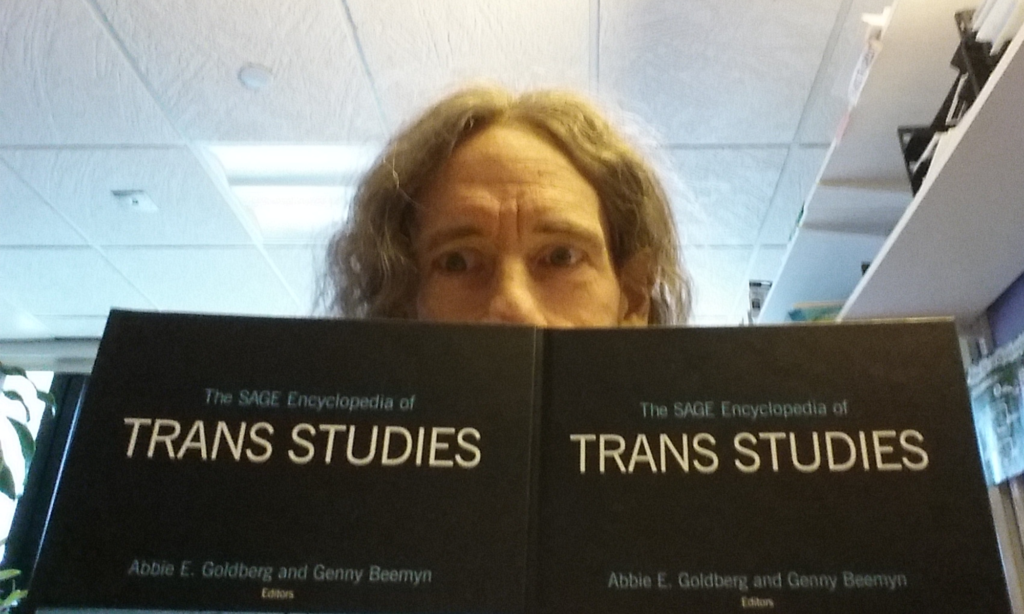 Genny looks over the top of The SAGE Encyclopedia of Trans Studies.